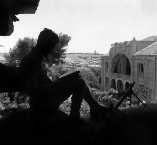 1948年,耶路撒冷一士兵在边境放哨时看书。